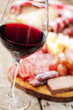 charcuter�a: Copa de vino tinto con el surtido de embutidos en el fondo