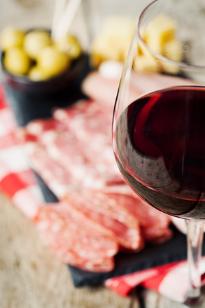 cheese platter: Glass of red wine with charcuterie assortment on the background Stock Photo