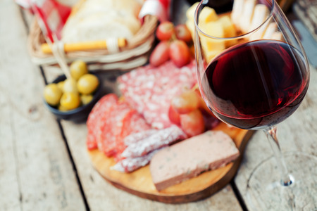 red food: Glass of red wine with charcuterie assortment on the background Stock Photo