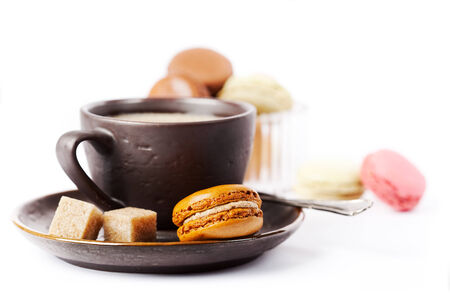 Cup of coffee and macaroons on white background, toned photo