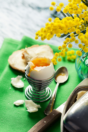 Breakfast setting with open soft boiled egg in egg cup