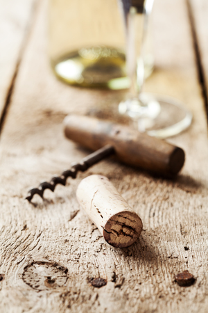 vins: Wine cork and corkscrew on wooden table, wine bottle and glass on the background Stock Photo