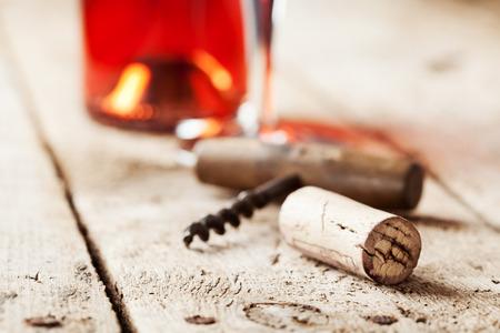 vino: Corcho del vino y sacacorchos en mesa de madera, botella de vino y el vidrio en el fondo