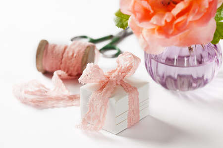 Decorated gift box and rose in vase on white