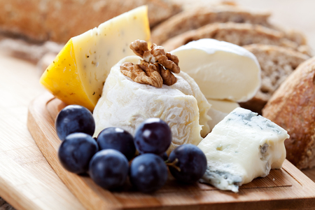tabla de quesos: Cheese platter: variety of cheeses on wooden plate with fruits and bread Foto de archivo