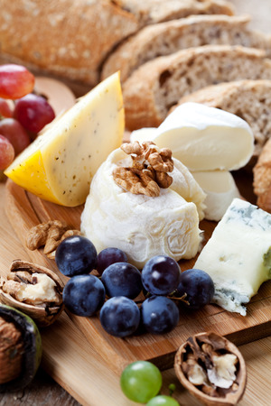 goat cheese: Cheese platter: variety of cheeses on wooden plate with fruits and bread Stock Photo