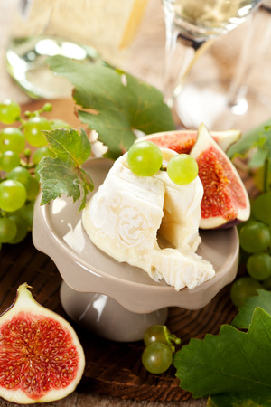 cheeseboard: Goat cheese on a stand with fruits
