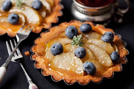 Homemade pear and blueberry tarts on black Stock Photo