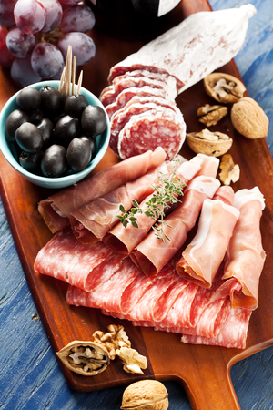 charcuter�a: Charcuterie assortment and black olives on wooden background