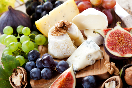cheese plate: Cheese platter: variety of cheeses on wooden plate with fruits Stock Photo