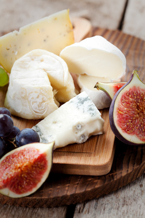 cheeseboard: Cheese platter: variety of cheeses on wooden plate with fruits Stock Photo
