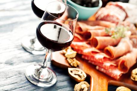 comida italiana: El vino tinto con el surtido de embutidos en el fondo