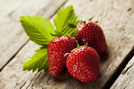 fresa: Fresas frescas deliciosas en el fondo de madera