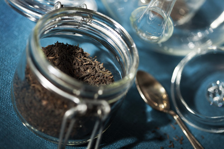 Jar with leaf tea and glass pot in the background Stock Photo
