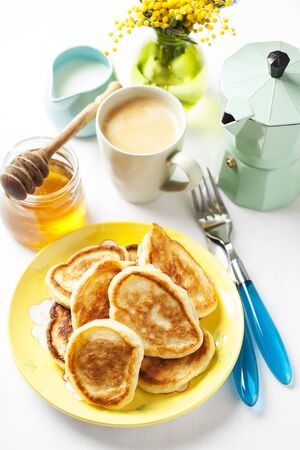 Breakfast setting with Russian style small pancakes, served with honey and coffee