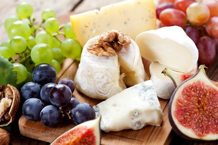 tabla de quesos: Disco del queso: variedad de quesos en plato de madera con frutas