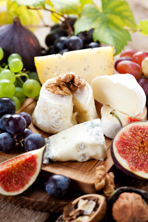 cheese platter: Cheese platter: variety of cheeses on wooden plate with fruits Stock Photo