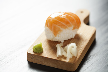 Sushi with wasabi paste and ginger on wooden board