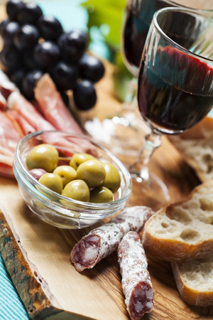 charcutería: Red wine with appetizer assortment on the background