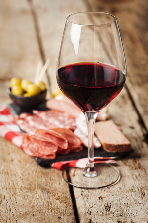 charcuterie: Glass of red wine with charcuterie assortment on the background Foto de archivo