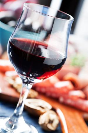 charcutería: El vino tinto y un surtido de embutidos en el fondo Foto de archivo