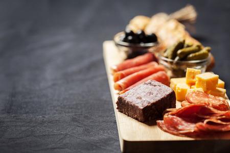 charcutería: surtido de embutidos, queso, aceitunas y pepinillos en tabla de madera