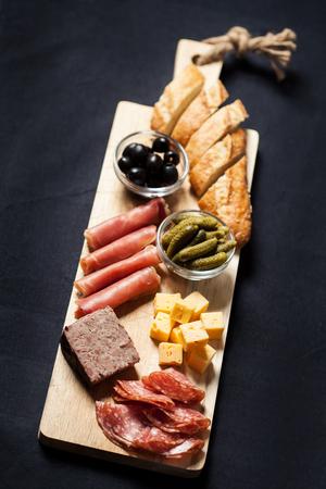 surtido de embutidos, queso, aceitunas y pepinillos en tabla de madera