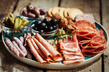 Charcuterie assortment, olives and gherkins on plate on wooden background