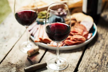 Rode wijn met charcuterie assortiment op de achtergrond