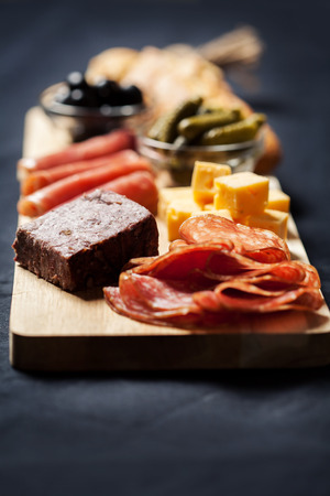 gherkins: Charcuterie assortment, cheese, olives and gherkins  on wooden board