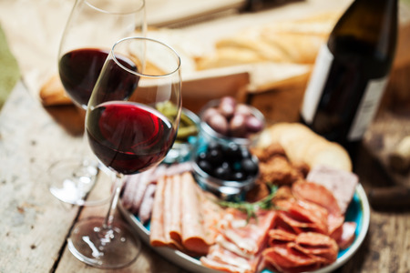 charcutería: Red wine with charcuterie assortment on the background