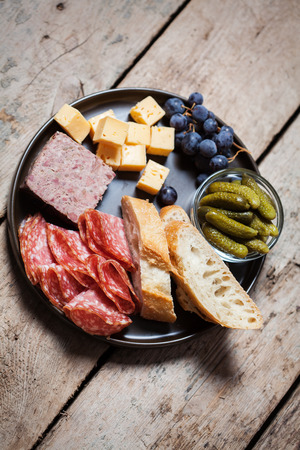 charcutería: surtido de embutidos, aceitunas y pepinillos en un plato sobre fondo de madera