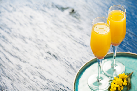 Two glasses with mimosa cocktail (cave plus orange juice) Stock Photo - 70345655