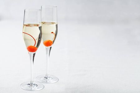 Two glasses of sparkling wine with maraschino cherries