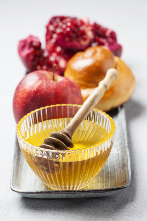 Rosh hashanah (jewish holiday) concept: honey, apple and pomegranate