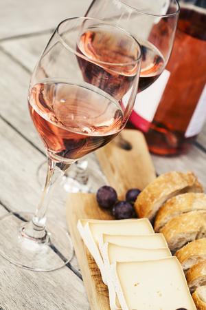 Twee glazen roze wijn en bord met fruit, brood en kaas op houten tafel, ondiepe DOF Stockfoto