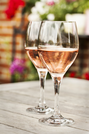 Two glasses of rose wine on wooden table with flowers on background