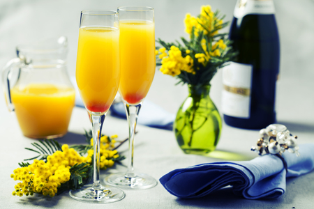 feast: Two glasses with mimosa cocktail (sparkling wine plus orange juice)