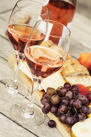 两杯玫瑰酒和水果,面包和奶酪在木桌上