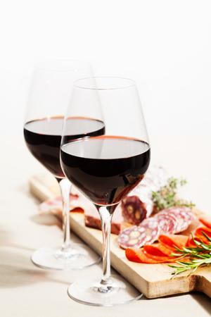 Surtido de vino tinto y embutidos en el tablero Foto de archivo