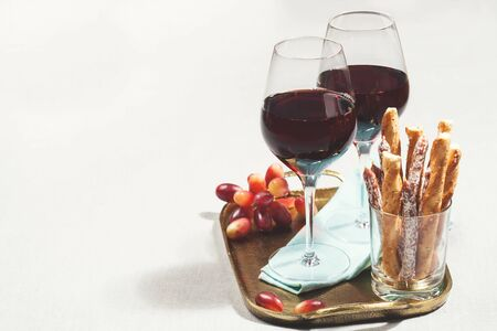 gressins: Two glasses of red wine with grapes and snacks Banque d'images