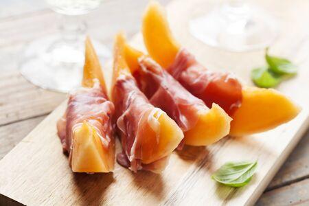 Cantaloupe: Slices of cantaloupe melon and prosciutto ham, shallow DOF