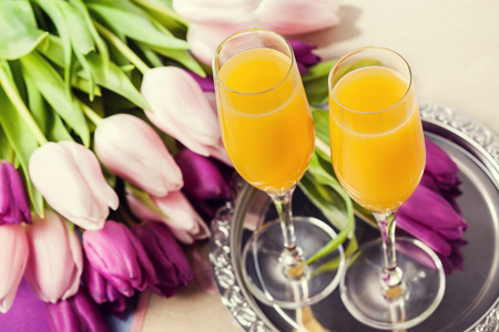 Two glasses of mimosa cocktail (champagne with orange juice) and tulips Stock Photo