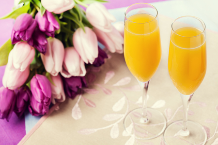 Two glasses of mimosa cocktail (champagne with orange juice) and tulips Standard-Bild