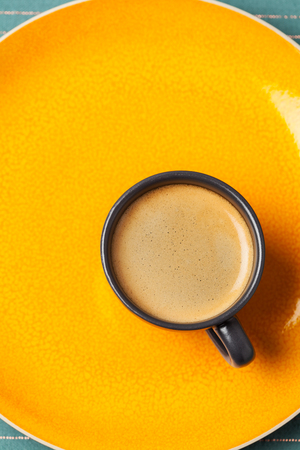 Cup of espresso on bright orange background