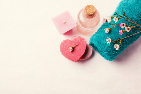 Spa setting with towel, soap, waxflowers and candle on pink background, toned Stock Photo