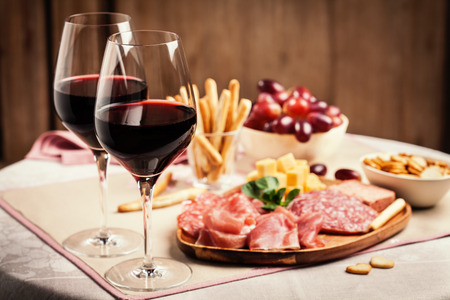 Two glasses of red wine with charcuterie, cheese, grapes and snacks