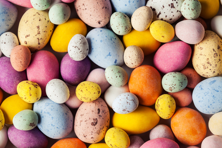 Colorful Easter chocolate eggs  in crispy sugar shell, background