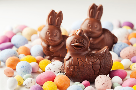 Easter chocolate hen and bunnies on colorful chocolate eggs background