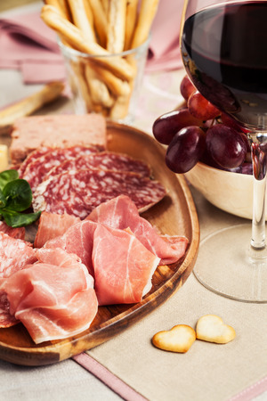 Red wine with charcuterie, cheese, grapes and snacks Фото со стока